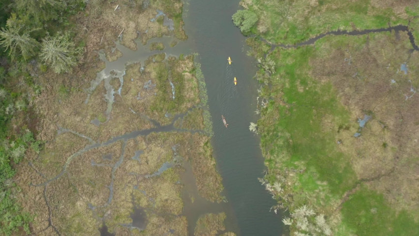 Far away top down drone shot of a canoe and two kayaks being paddled through an estuary