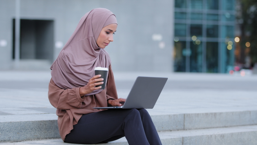 Muslim business woman islamic girl student freelancer user arab lady worker client sitting on sidewalk in city outdoors browsing net shopping online working laptop drinking tea take away coffee drink Royalty-Free Stock Footage #1078457948