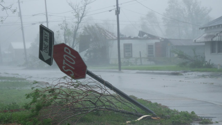 Houma, Louisiana USA - August 29 2021: Hurricane Ida Blows Over Stop Sign While A Damaged Building With No Roof Sits In the Background