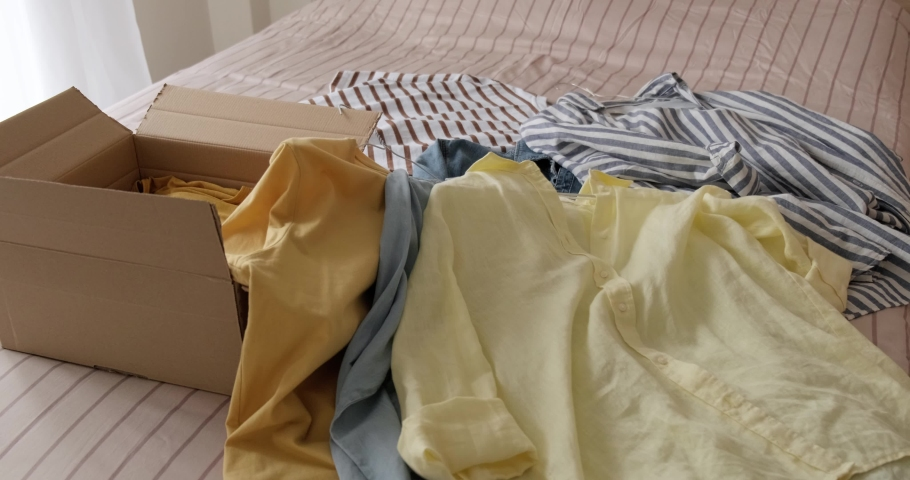 Bunch of used clothes being packed in carboard box, reusable clothing, concept of second hand resale or donation.  Royalty-Free Stock Footage #1078547894