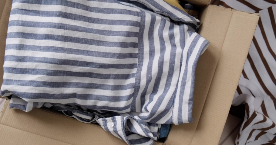 Bunch of used clothes being packed in carboard box, reusable clothing, concept of second hand resale or donation.  Royalty-Free Stock Footage #1078565789
