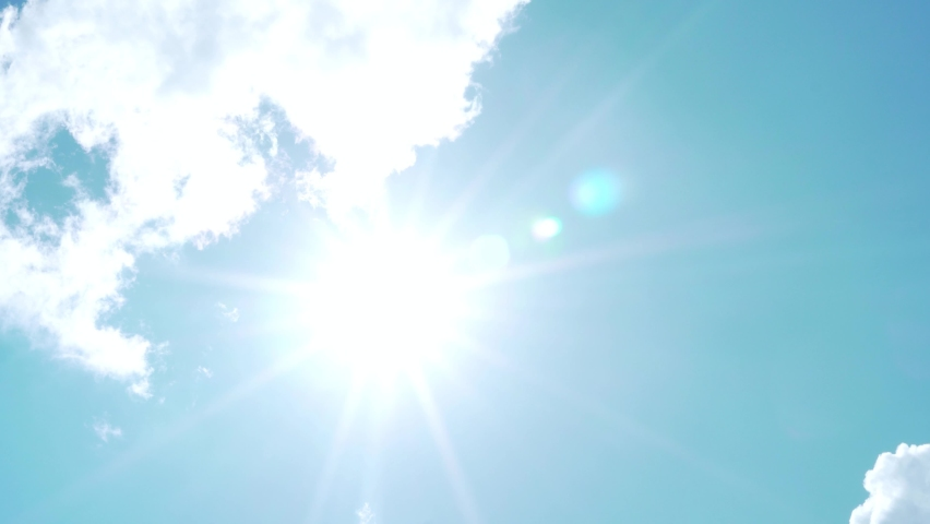 Sun Shines in the Azure Sky on a Clear Sunny Day and White Flying Puffy Clouds, Timelapse. Sunlight, Glare and Rays of the Sun Blue Sky and White Clouds, Beautiful Lapse Time. Sunbeam  Sun Ray Flares