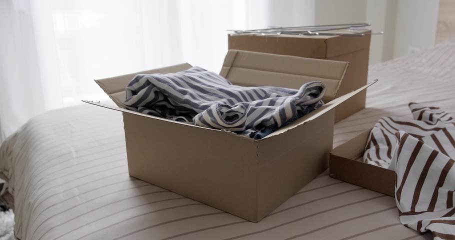 Bunch of used clothes being packed in carboard box, reusable clothing, concept of second hand resale or donation.  Royalty-Free Stock Footage #1078795058