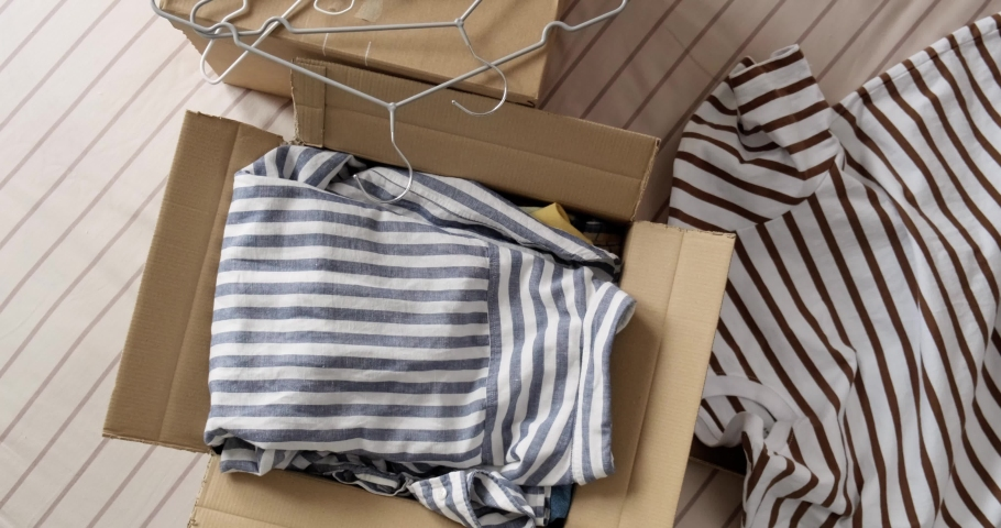 Bunch of used clothes being packed in carboard box, reusable clothing, concept of second hand resale or donation.  Royalty-Free Stock Footage #1078904828