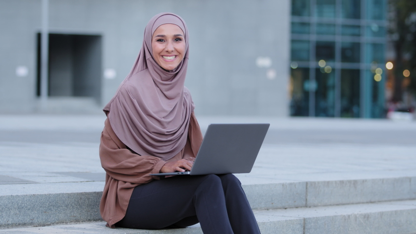Beautiful muslim girl in hijab scarf islamic woman using wireless laptop working outdoors looking at camera positively smiling. Successful arabian female freelancer university student studying in city Royalty-Free Stock Footage #1078907057