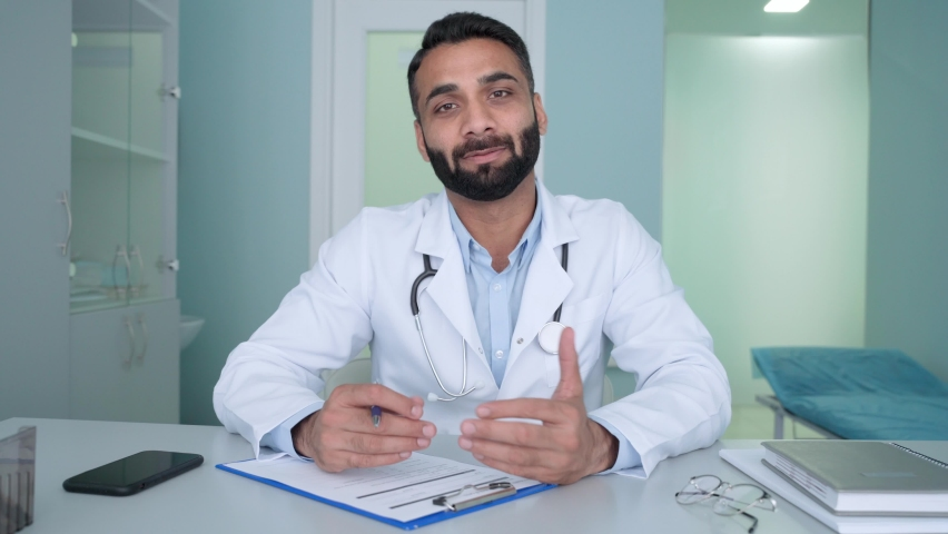 Indian latin male happy positive gp doctor in modern clinic wearing white coat uniform talking using laptop computer having videocall chat, consulting remotely. Telemedicine concept. Webcam view. Royalty-Free Stock Footage #1079017712