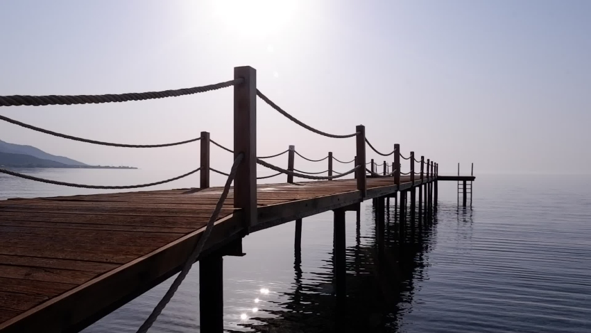 Perspective view of wooden pier stretching out to calm sea at sunrise. A calming sea view. HD.   Shutterstock HD Video #1079054030