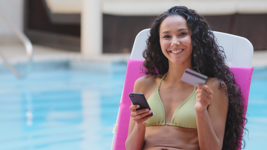 Safe mobile banking. Smiling latina lady in swimsuit hold phone credit bank card do online shopping provide internet payment. Happy young woman enjoy easy fast secure transferring money in ebank app Royalty-Free Stock Footage #1079088434