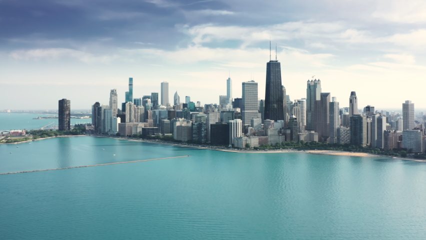 Amazing clear and vibrant blue waters of Michigan lake in Illinois with breathtaking Chicago downtown cityscape on background. Cinematic aerial Chicago coastline on sunny summer day with copy space
