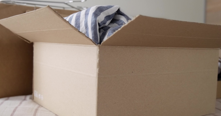 Bunch of used clothes being packed in carboard box, reusable clothing, concept of second hand resale or donation.  Royalty-Free Stock Footage #1079216150