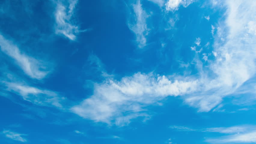 White clouds moving across the blue sky against a background of the sun. Time lapse | Shutterstock HD Video #10792214