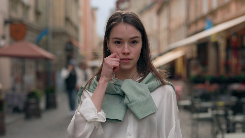 Young woman with hearing loss gesturing with fingers no to racism phrase while standing on street and looking at camera. Caucasian brunette using sign language during social movement outdoors. | Shutterstock HD Video #1079231150