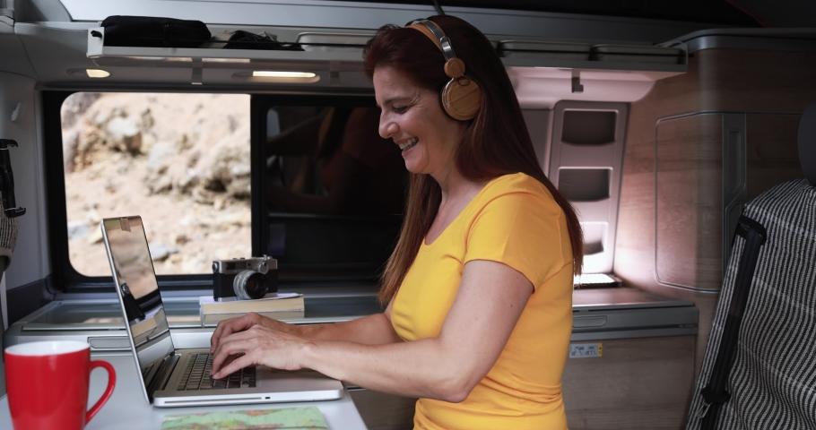Caucasian mature woman using laptop inside mini van  on a road trip  | Shutterstock HD Video #1079259515