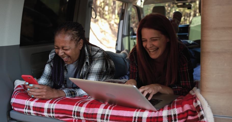 Mature multiracial women using computer laptop and mobile phone inside mini van  - Travel, vacation and technology concept | Shutterstock HD Video #1079259521