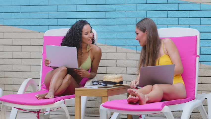 Different ethnicity cheerful young female friends give high five buddies gesture. Caucasian Hispanic freelance using laptops by hotel summer pool. Greeting, celebrate congratulate great news concept | Shutterstock HD Video #1079260352