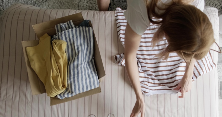 Top view of woman packing used casual clothes into box to sell online as second hand or donation, sustainable living concept. Royalty-Free Stock Footage #1079267183
