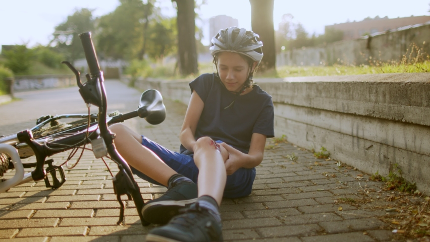 Boy feeling pain after he felt from bicycle and injured knee on street in city. Injury looks deep and serious. He wears protective helmet | Shutterstock HD Video #1079271707