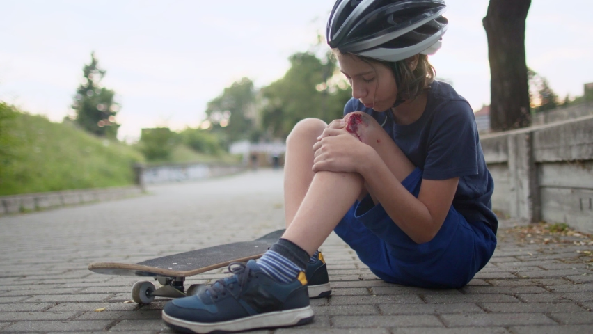 Boy feeling pain after he felt from skateboard and injured knee on street in city. Injury looks deep and serious. He wears protective helmet | Shutterstock HD Video #1079271779