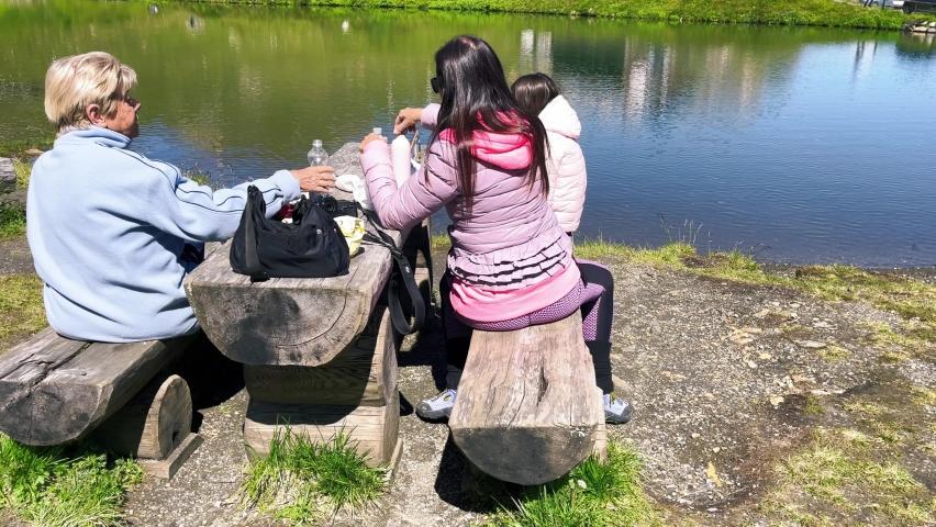 Happy family having a picnic at wonderful alpin lake. | Shutterstock HD Video #1079274884