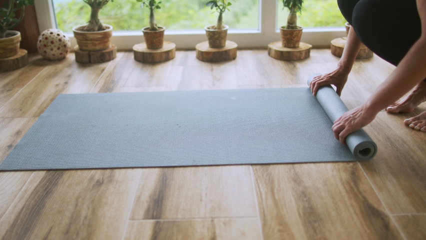 Woman is finishing yoga class on terrace at home and rolling exercise mat. She is mature adult and very fit and vital | Shutterstock HD Video #1079276621