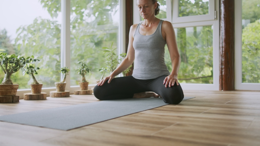 Woman is doing yoga on terrace at home. She is stretching on exercise mat. She is mature adult and very fit and vital | Shutterstock HD Video #1079276639