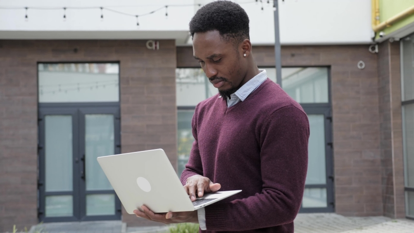 Thoughtful businessman black man millennial wearing casual clothes standing outdoors typing on laptop, concerned about problem, guy thinking making difficult decision looking away, planning strategy. Royalty-Free Stock Footage #1079280566
