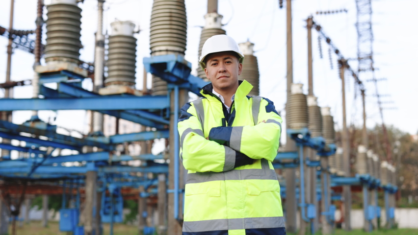 Portrait of young smiling asian electric worker with arms folded at power site. Portrait of engineer worker in hard hat standing at high voltage power station | Shutterstock HD Video #1079284151