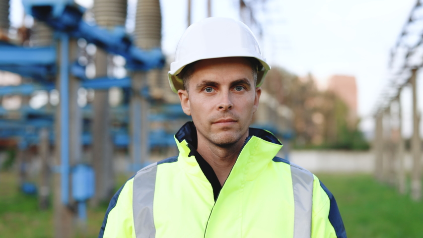 Caucasian adult engineer in helmet look at camera at high voltage power station outside. Positive worker. Ecological industry. Electric power plant concept | Shutterstock HD Video #1079284154