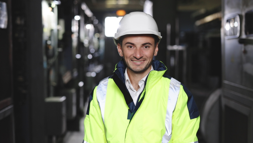 Happy Professional Heavy Industry Engineer Worker Wearing Uniform and Hard Hat in a Steel Factory. Smiling Caucasian Industrial Specialist Standing in a Metal Construction Manufacture | Shutterstock HD Video #1079284166