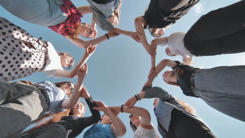 A group of girls makes a circle shape holding each other's hands. | Shutterstock HD Video #1079311955