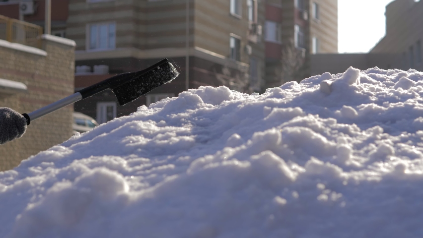 A guy cleans fresh snow from his car with a brush on a bright sunny day.Cleaning the car roof and mirror in winter weather from snow and ice. The streets are covered with snow and snowdrifts.