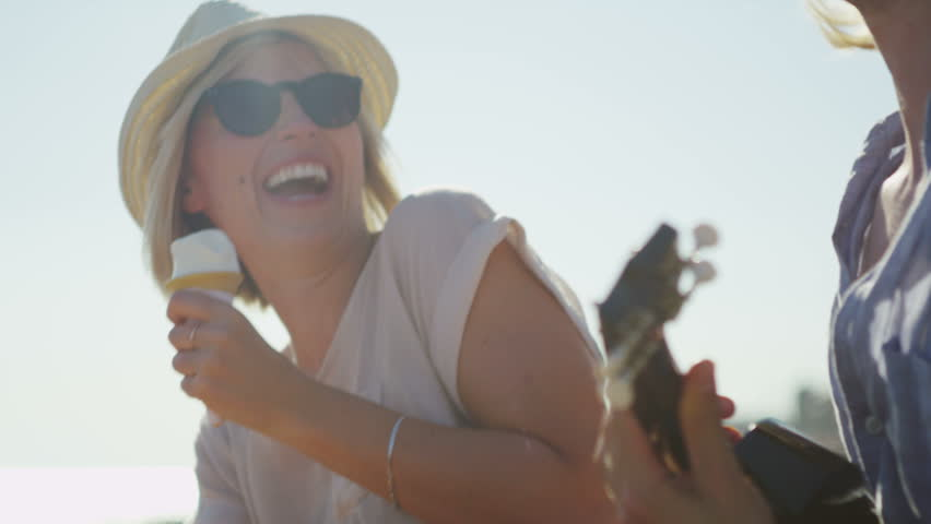4K Young couple on the beach having fun with music and ice cream, shot on RED EPIC #10794329