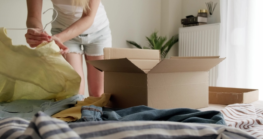 Woman packing used casual clothes into box to sell online as second hand or donation, sustainable living concept. Royalty-Free Stock Footage #1079448686