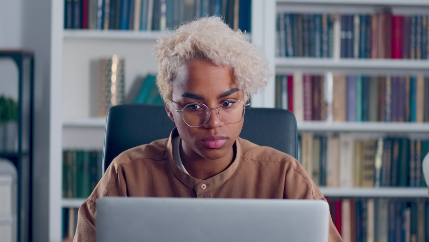 Close up concerned African American woman looking thoughtful on laptop computer thinking solving problem at home office. Serious female search for inspiration makes decision feel lack of ideas. Royalty-Free Stock Footage #1079678768