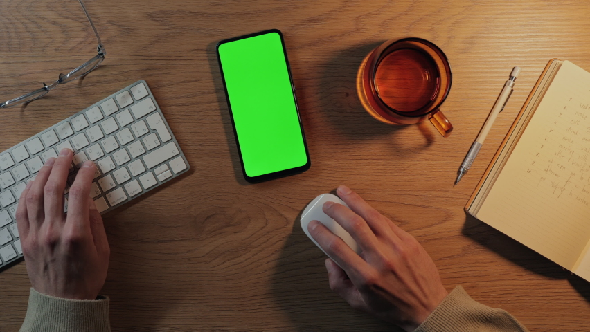 Top view of male hands typing on wireless keyboard and using computer mouse. Daily planner, cup of coffee and modern smartphone lying on table. Focus on chroma key screen of mobile. Royalty-Free Stock Footage #1079838419