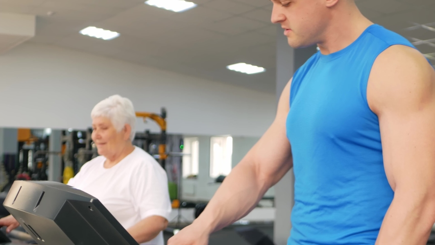 Happy smiling people are engaged in physical education, simulators in the gym. Active healthy lifestyle, senior concept. A woman with gray hair, a young coach is a muscular man. portrait   Shutterstock HD Video #1080822209