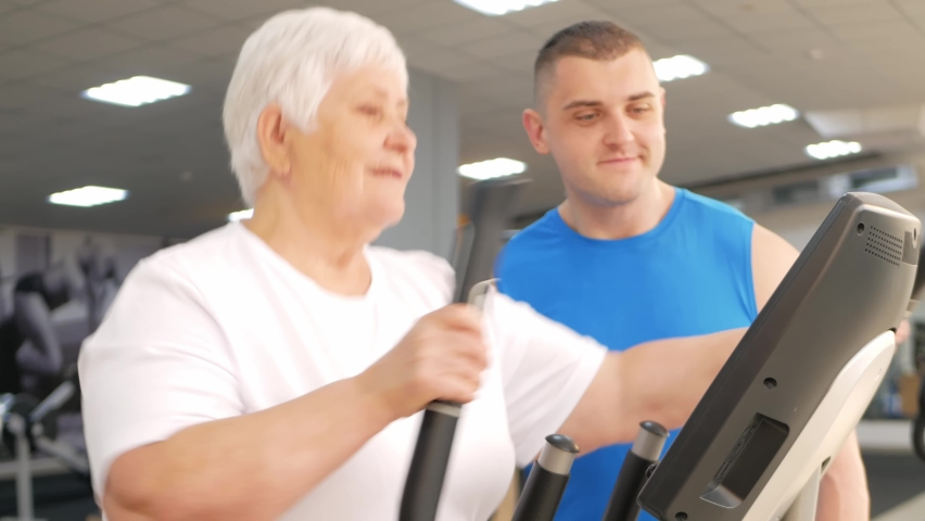 Happy smiling people are engaged in physical education, simulators in the gym. Active healthy lifestyle, senior concept. A woman with gray hair, a young coach is a muscular man.   Shutterstock HD Video #1080822212