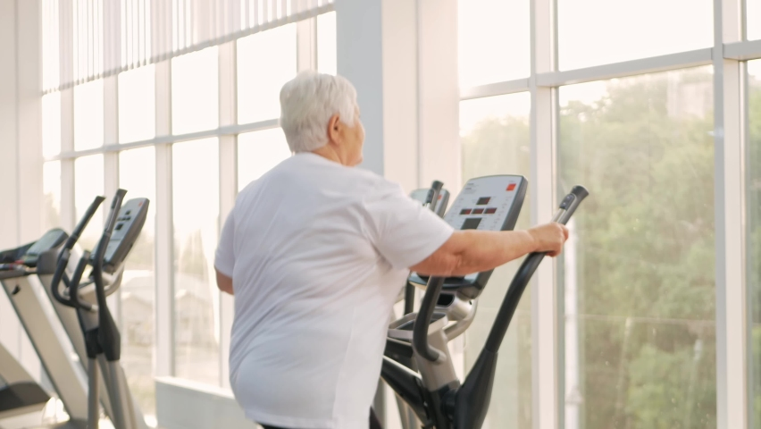Elderly retired woman with gray hair is engaged in sports on simulators in gym. Healthy lifestyle, senior concept, indoor. Rehabilitation, treatment after injuries, improvement. Individual portrait   Shutterstock HD Video #1080822215
