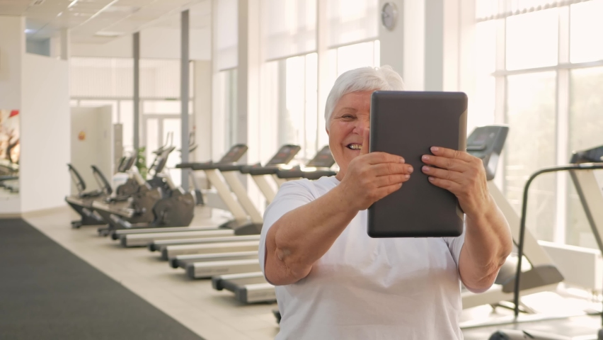 An elderly woman is photographed on a tablet, video call, rest after training, sends greetings to friends, communication and social networks, the Internet. Smiling   Shutterstock HD Video #1080822218