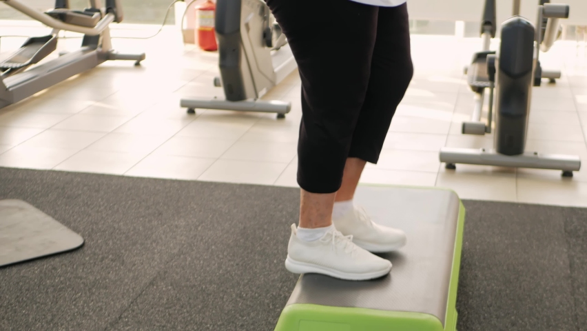 Pensioner, elderly woman in a gym on a step platform. Simulator, young coach. Happy smiling people, healthy sports lifestyle, senior concept, indoor. Rehabilitation, treatment, physical body positive   Shutterstock HD Video #1080822221