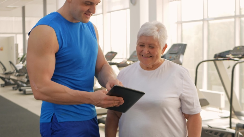 An elderly woman is photographed on a tablet, video call, rest after training, sends greetings to friends, communication and social networks, the Internet. coach shows results   Shutterstock HD Video #1080822224