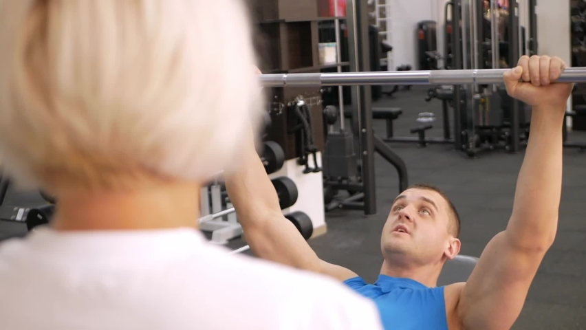 An elderly woman, eldest is engaged in sports in gym. Muscles swing barbell. Retired concept, healthy lifestyle, indoor. The trainer helps and teaches correct performance of the exercise. close up   Shutterstock HD Video #1080822770