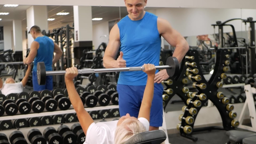 An elderly woman, eldest is engaged in sports in gym. Muscles swing barbell. Retired concept, healthy lifestyle, indoor. The trainer helps and teaches correct performance of the exercise. thumbs up   Shutterstock HD Video #1080822773