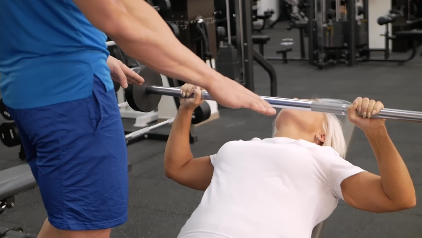 An elderly woman, eldest is engaged in sports in gym. Muscles swing barbell. Retired concept, healthy lifestyle, indoor. The trainer helps and teaches correct performance of the exercise.   Shutterstock HD Video #1080822776