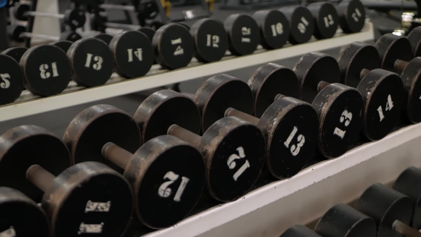 Kettlebells dumbbell with different weights are on the stand in the gym, footage screensaver sports   Shutterstock HD Video #1080822779