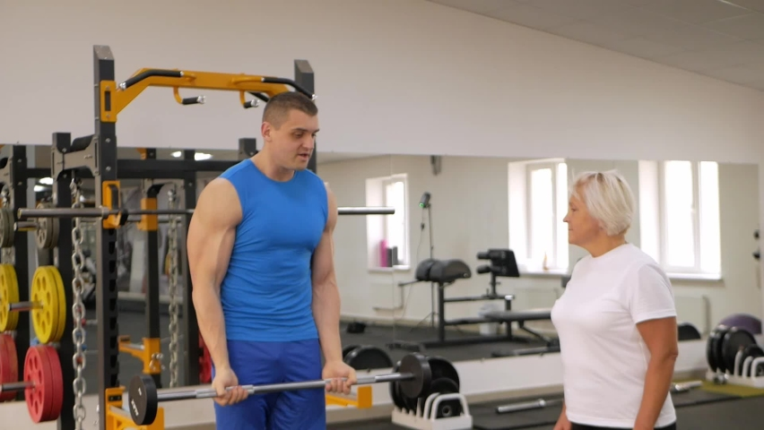 An elderly woman is engaged in a sport in the gym. The trainer helps and explains how to perform the exercise. healthy lifestyle, pensioner, concept, indoor. Sports training. rod   Shutterstock HD Video #1080822782