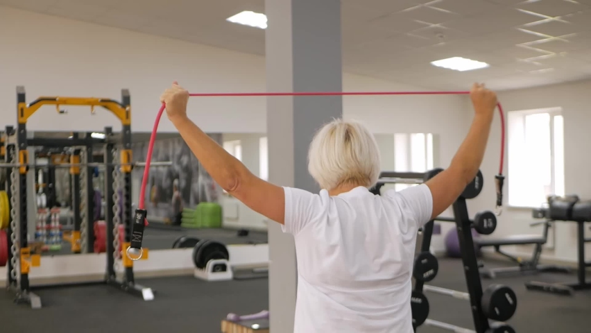Elderly woman with gray hair plays sports in gym. Active healthy lifestyle, pensioner, senior concept. Rehabilitation after injuries, strengthening immunity, losing weight, arm stretching, back   Shutterstock HD Video #1080822797