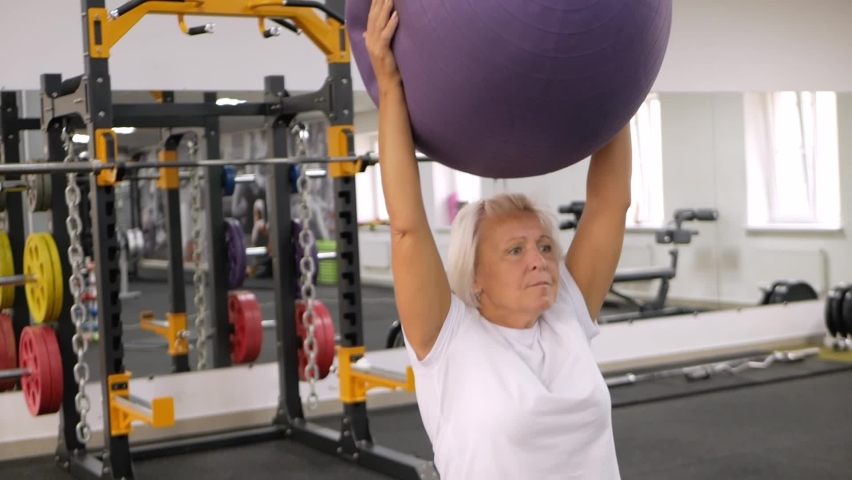 Elderly woman with gray hair plays sports in gym. Active healthy lifestyle, pensioner, senior concept. Rehabilitation after injuries, strengthening immunity, losing weight, gymnastic ball   Shutterstock HD Video #1080822803