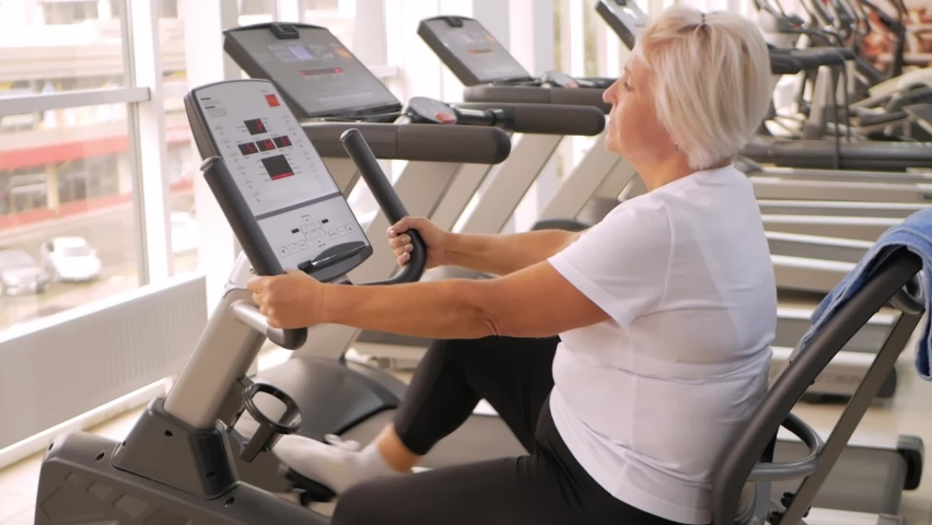 Rehabilitation center gym, recovery from injuries and fractures. an elderly woman perform an exercise on the simulator. Healthy lifestyle, concept senior, pensioner. fat client   Shutterstock HD Video #1080822812