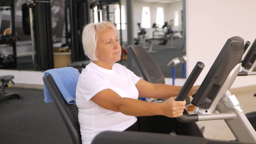 Rehabilitation center gym, recovery from injuries and fractures. an elderly woman perform an exercise on the simulator. Healthy lifestyle, concept senior, pensioner. Smiling   Shutterstock HD Video #1080822821